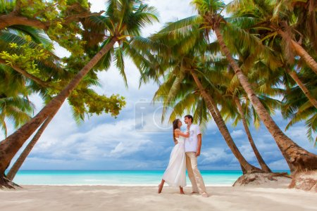 Photo for Young loving happy couple on tropical beach with palm trees, wedding on beach - Royalty Free Image