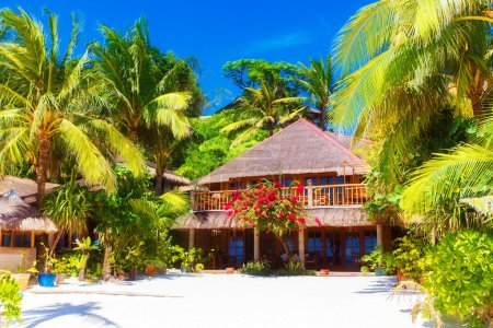 Beautiful house to a reed roof standing on a white, sandy beach