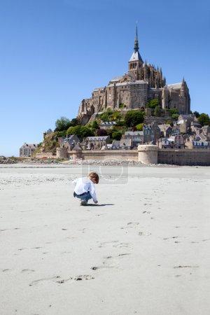 Der Junge spielt auf dem Sandplatz