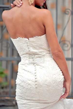 Close up of bride back with white dress and earrings