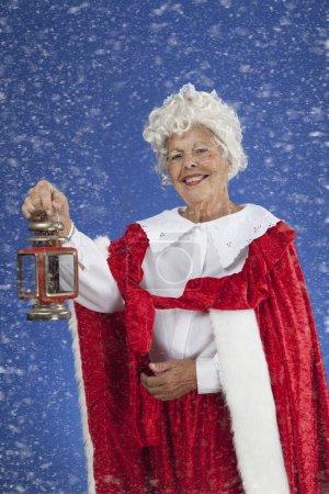 Photo pour Image de couleur verticale, de Mme Noël debout dans la neige tout en tenant une lanterne - image libre de droit