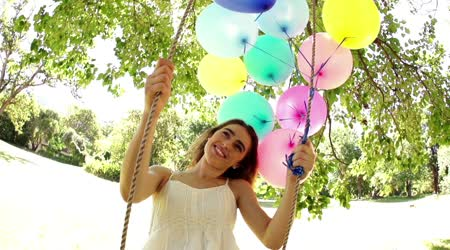 Woman smiling while holding balloons