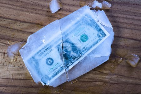 Photo pour Un billet d'un dollar gelé et cassé dans la glace et l'argent prêté . - image libre de droit