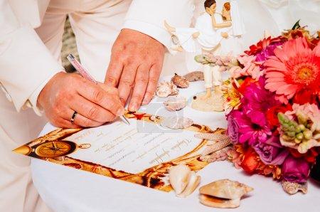 Photo pour Gros plan marié et mariée écrire sur l'enregistrement du mariage. Mariage sur la plage. Nouveaux mariés signant une licence de mariage ou un contrat de mariage - image libre de droit