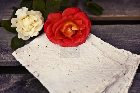 Photo pour Beautiful red and yellow-white roses with letter for copy space on wooden rustic background. Summer floral background - image libre de droit