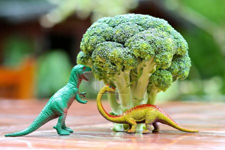 Funny picture of toy dinosaur eating broccoli tree. Photo can be used to help cooking with children, preparing kid-friendly dishes and promoting healthy food for children