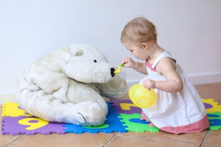 Photo for Cute blonde toddler girl feeding her big white teddy bear with porridge from spoon sitting indoors at home or kindergarten - Royalty Free Image