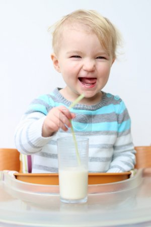 Girl drinking milk from the glass with straw