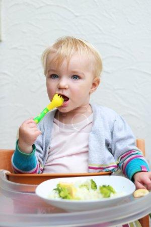 Girl eating boiled vegetables with plastic fork
