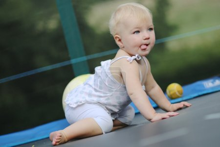Baby girl crawling on trampoline with balls