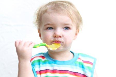 Girl wearing colorful bib eating porridge with spoon