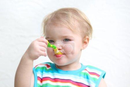 Girl eating porridge with spoon