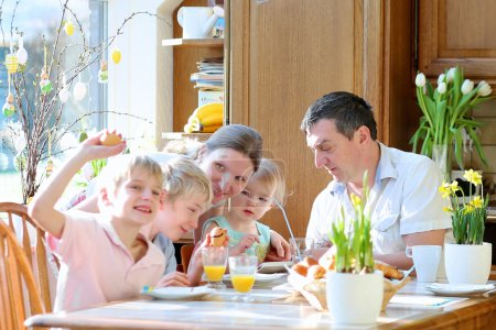 Family of five: father, mother and three kids, teenager sons and toddler daughter eating eggs during family breakfast on Easter day sitting together in sunny kitchen. Selective focus on little girl.