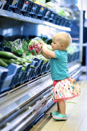 Cute baby girl is picking up radish pack from a shelf in vegetables department in a supermarket