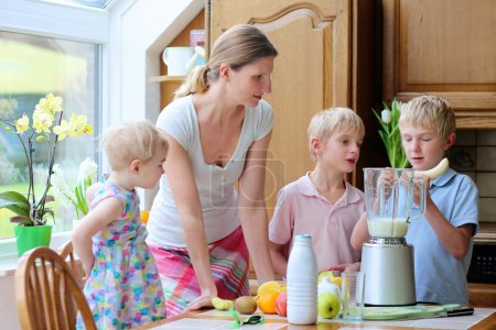 Mother with three kids preparing healthy drink with milk and fruits