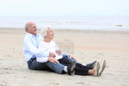 Couple sitting  on sandy peaceful beach