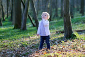 Toddler girl playing in spring forest