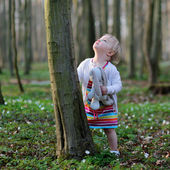 Girl playing in spring forest on a sunny day