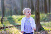 Girl playing in spring or summer forest on a sunny day