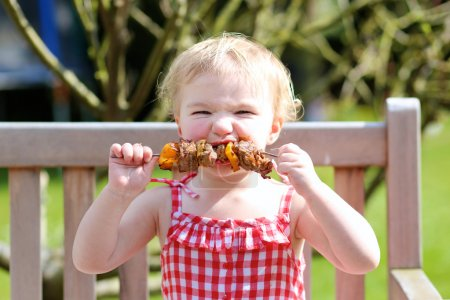 Photo for Funny child, adorable blonde toddler girl in red gingnam style dress messy around mouth eating delicious meat made on barbeque sitting outdoors in the garden on a wooden chair on a sunny summer day - Royalty Free Image