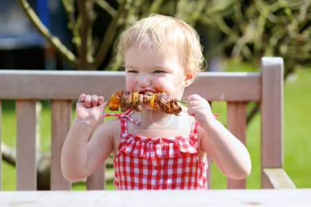 Photo for Funny child, adorable blonde toddler girl in red dress messy around mouth eating delicious meat made on bbq sitting outdoors in the garden on a wooden chair on a sunny summer day - Royalty Free Image