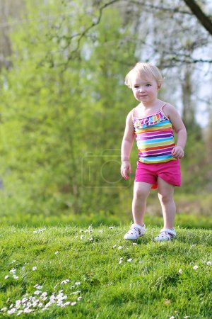 Little child playing in the park on a sunny summer day
