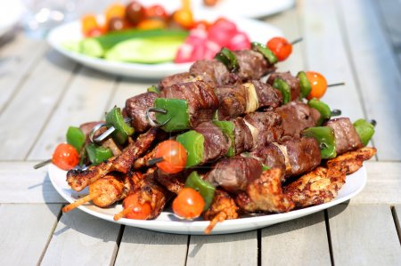 Photo for Assorted delicious grilled meat with vegetable on white plate on picnic table for family bbq party - Royalty Free Image