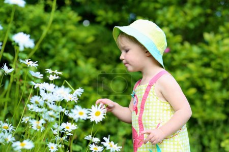 Pretty little girl playing in the garden with daisies flowers