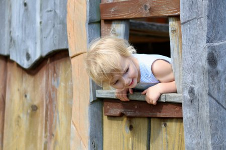 Funny little girl playing in wooden house