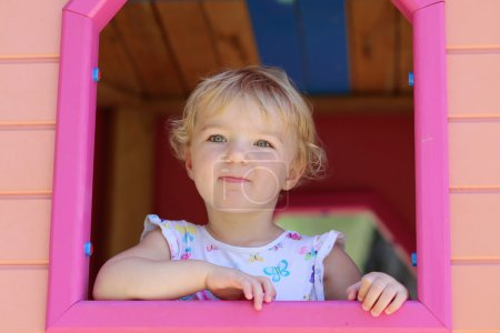 Happy little girl having fun in playhouse on a summer day