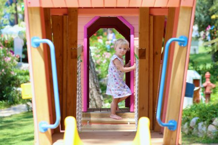 Photo for Happy child, adorable blonde toddler girl, having fun outdoors hiding in plastic playhouse in playground on a sunny summer day - Royalty Free Image