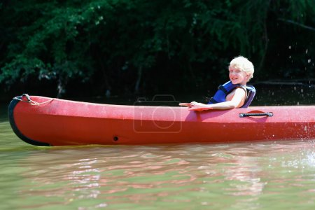 Active happy teenage boy kayaking on the river