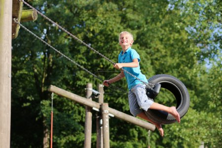 Photo for Happy child, teenage school boy, having fun outdoors swinging on tire in playground on a sunny summer day - Royalty Free Image