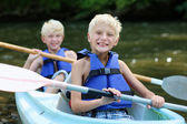 Two happy school boys kayaking on the river