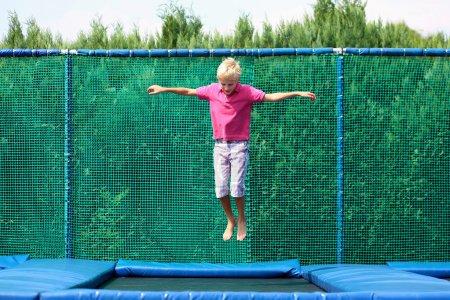 Happy school boy jumping on trampoline