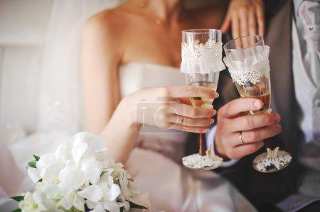 Photo pour Mariée et marié tenant des lunettes de mariage magnifiquement décorées avec champagne - image libre de droit