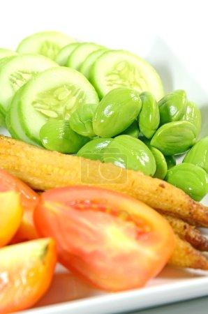 Photo pour Mixte légume menu avec des tranches de concombre, tomates, grillé mini-maïs, bouilli de gombo et puent frais haricots surtout servis avec une sauce crevettes-coller dans le menu de cuisine thaïlandaise. - image libre de droit