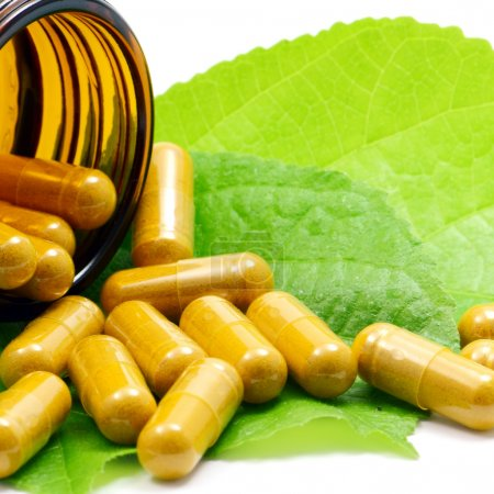 Photo for Tumeric Powder in Transparency Hard Gelatin Capsules Contain in Amber Glass Light resistant Bottle Displayed with Green Natural Leaves on White Background. - Royalty Free Image