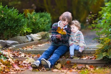 Photo for Brother and his little baby sister talking and playing with orange maple leaves sitting on old stone stairs in a beautiful autumn park - Royalty Free Image