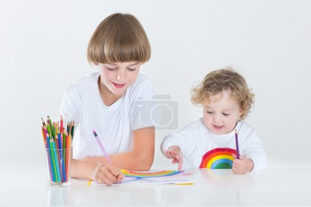 Photo for Cute toddler girl drawing with colorful pencils and her brother watching and smiling - Royalty Free Image