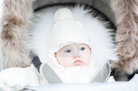 Sweet little baby sitting in a winter fur stroller