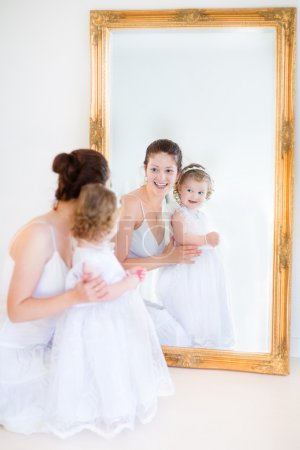 Mother and her toddler daughter standing in front of a big mirror