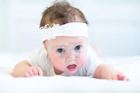 Photo pour Bébé fille drôle avec un arc blanc - image libre de droit