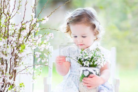 Girlsitting in a white rocking chair holding first spring flowers
