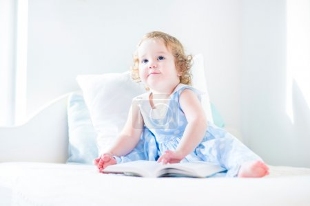 Little toddler girl reading a book