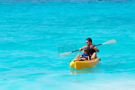 Photo for Father and son on a kayak ride in a tropical blue sea - Royalty Free Image