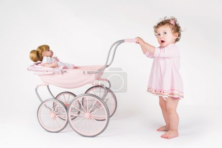 Baby girl walking with a doll stroller