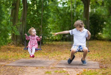 Photo for Brother and little baby sister playing together on a swing on a playground in a park on a warm nice autumn day - Royalty Free Image