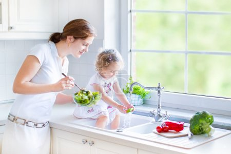 Mother and her daughter washing vegetables