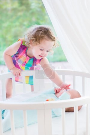 Toddler girl playing with newborn brother